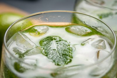 Closeup of a green mint leaf with ice in a mojito drink